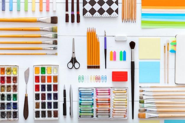 Принадлежности, установленные на настольном виде, креативные инструменты для школьной креативной работы на белом деревянном столе, фон с нанесением живописи, канцелярские принадлежности, цветные краски, кисти, карандаши, мелки, копирование пространства, плоская планировка