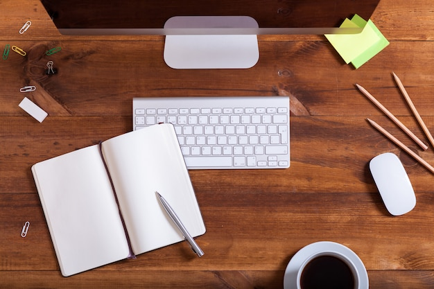 上からコンピューター上面のオフィスデスク、デスクトップモニターキーボード付きのモダンな作業テーブルノートブックとコーヒーを開き、機器や作業または教育の概念、ビジネス職場のための供給