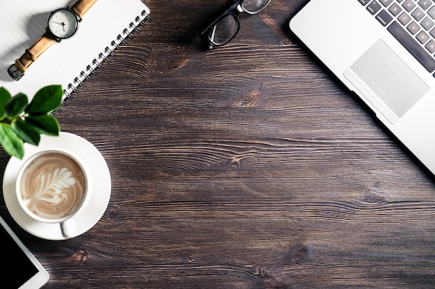 Бизнес рабочий стол с ноутбуком и телефоном блокнот очки смотреть на темный деревянный стол, современный стол на рабочем месте фон с устройствами и чашка кофе, вид сверху сверху
