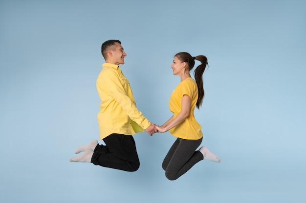 一緒に手を繋いでいるジャンプとお互いを見て黄色のシャツで幸せなカップル