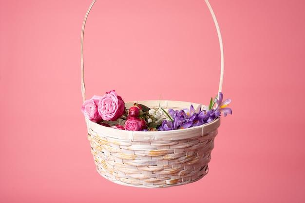 Корзина из весенних цветов на розовом