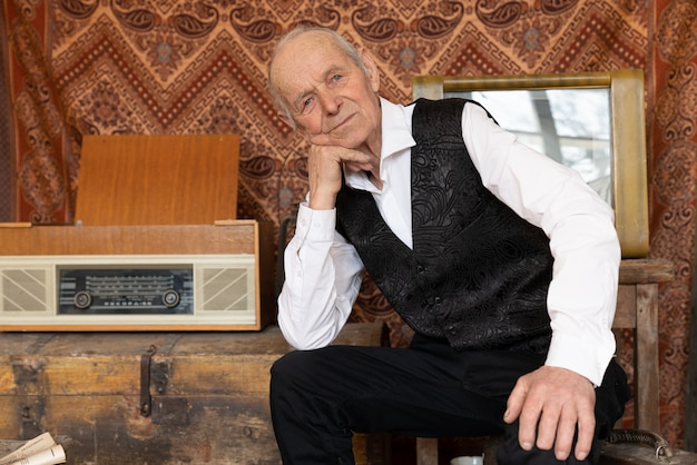 Элегантный старший мужчина оперся на руку и смотрит в камеру, сидя в своей винтажной комнате