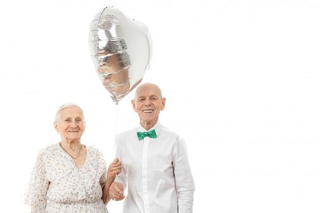 Пожилая пара держит воздушный шар в форме сердца из серебра