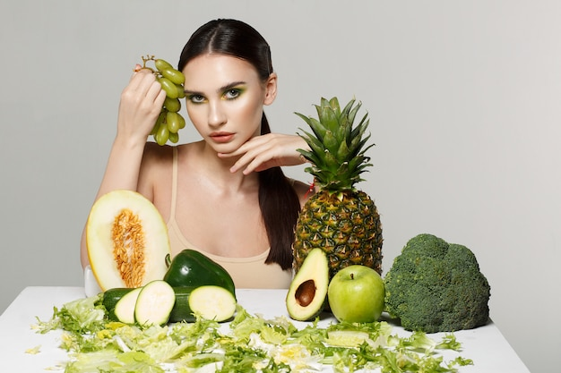テーブルの上の果物と野菜の美しい若いブルネットの女性の写真