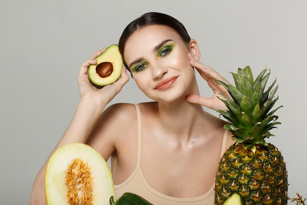 果物と野菜のテーブルでポーズブルネットの少女