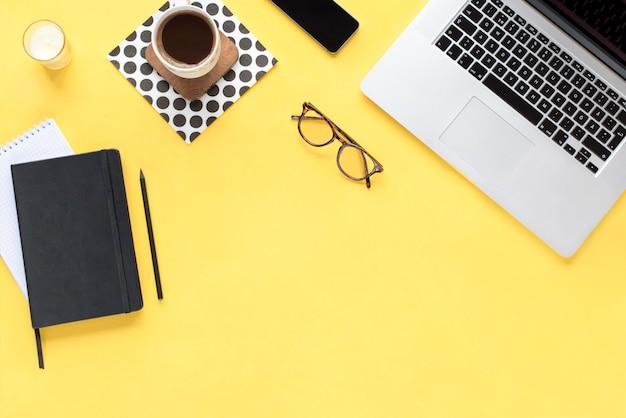 ホームオフィスデスク。黄色の背景上のコンピューターとワークスペース。フラット横たわっていた、トップビュー。ファッションブログルック。テキストを追加します。