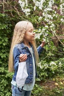 金髪の美しい少女がマスクを脱いで、春になると咲く木を嗅ぎます