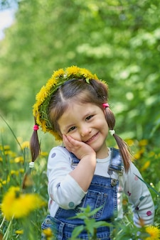 Девушка с двумя хвостами сидит в поле одуванчиков.