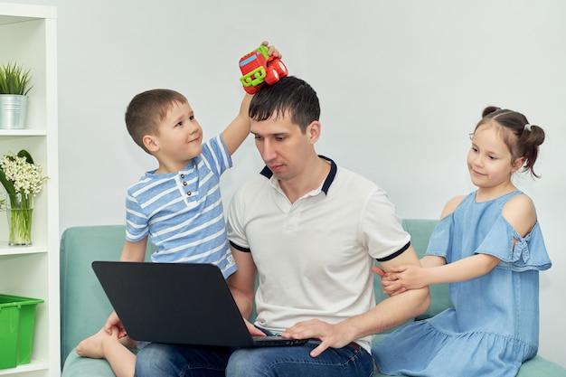 Фрилансер работает на дому в комфортных условиях. человек пытается работать, ребенок мешает отцу работать.
