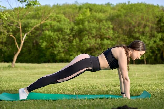 自然でヨガを練習する前に屋外でストレッチを行う運動の女の子