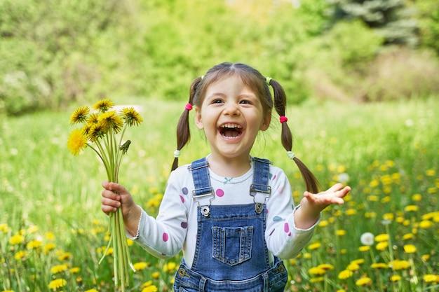 Красивая девушка с двумя хвостами держит букет одуванчиков и смеется