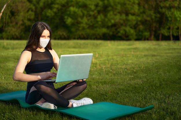 芝生の上のラップトップで座っている医療マスクの女の子