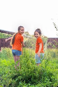 Дети летом поливают сад из-под шлангов.