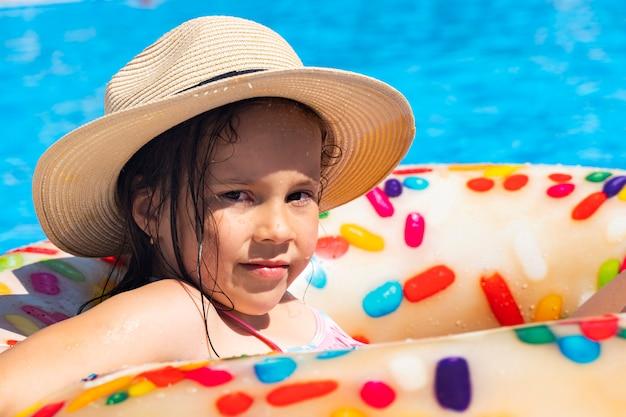 Дети сидят на надувном кольце в бассейне.