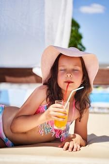 女の子はビーチにあり、喜びでジュースを飲む