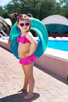 Маленькая девочка с плавательный круг в купальнике стоит у бассейна.