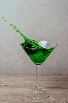 Всплеск в стакан зеленого алкогольного коктейля с лаймом, мятой и кубиком льда на сером фоне градиента