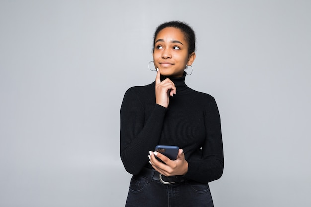 Портрет латинской женщины, держащей мобильный телефон и смотрящей рукой на подбородок