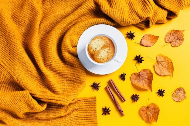 Осенняя композиция. кофе и сухие листья на желтом столе.