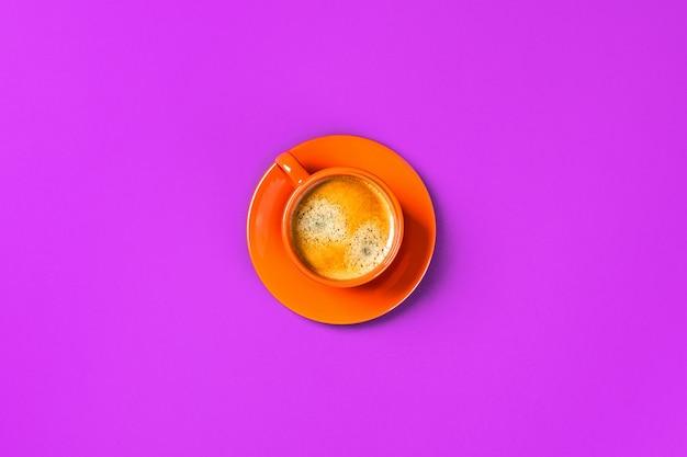 Одна чашка кофе на фиолетовом столе.