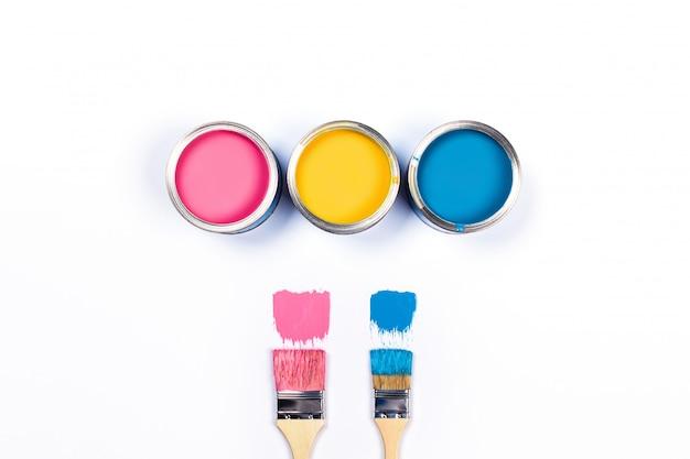 Белый стол с тремя цветными краской банки и кисти.