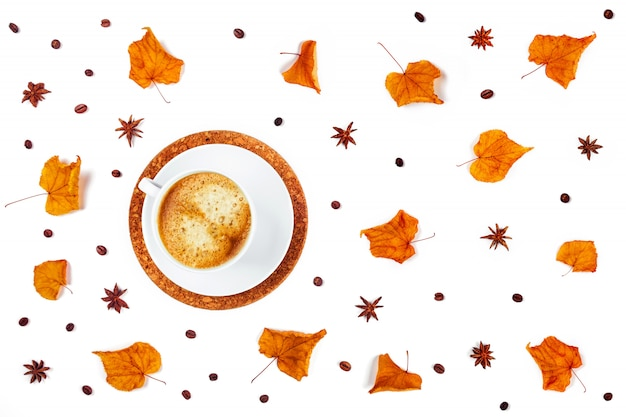 Белая чашка кофе в окружении листьев и звездчатого аниса.