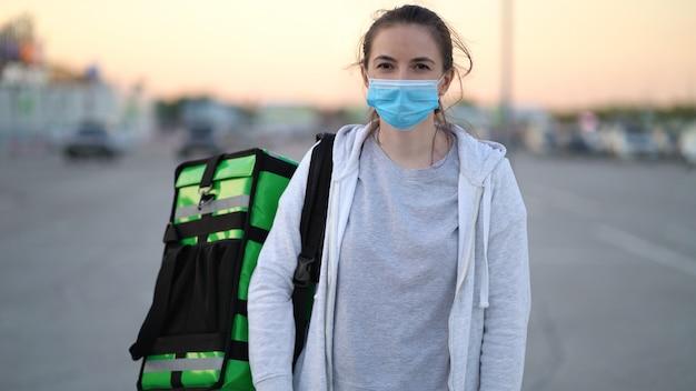 医療用マスクを着用した若い宅配便がお客様に注文品を配送しています。