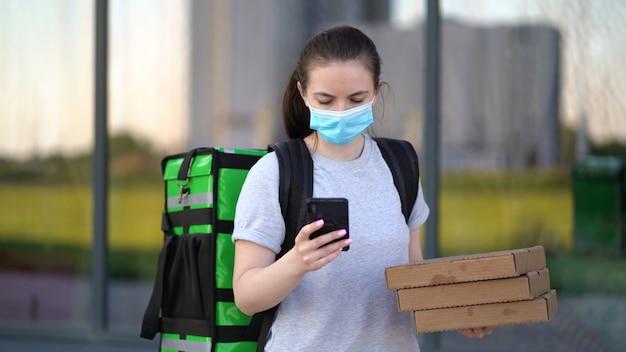 若いピザ宅配便が注文を配信しています。医療マスクで段ボール箱を保持している電話で配達の女性。