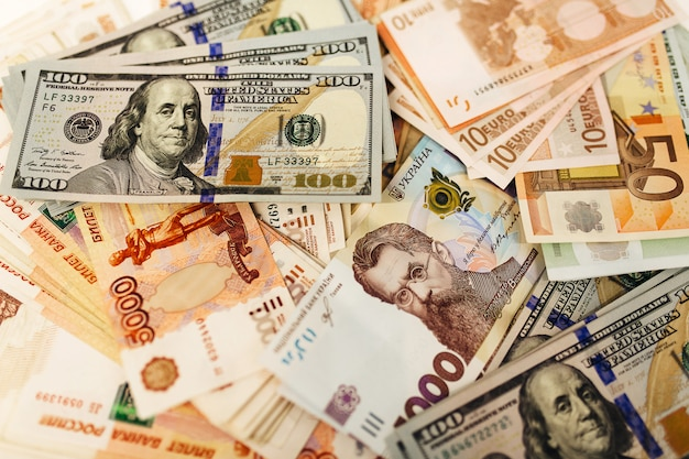 テーブルの上のさまざまな国からのお金のパック。ドル、ユーロ、グリブナ、ロシアルーブル、為替レート。