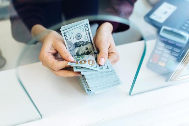 お金の紙幣を数える女性。お金、銀行、通貨、外国為替レートの概念写真