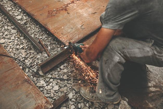 Мужчина режет железо на улице.