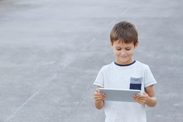 デジタルタブレットコンピューターと微笑む少年。