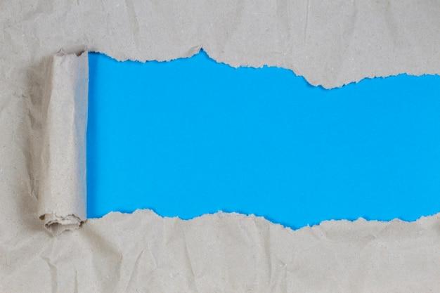 明るい青の背景を明らかにするために引き裂かれた茶色のパッケージ紙