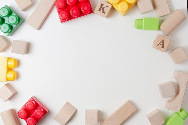 Красочные пластиковые и деревянные кубики на белом фоне