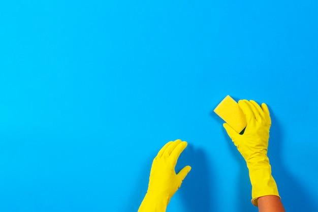 Руки в желтых перчатках с губкой на синем фоне. уборка, дезинфекция дома