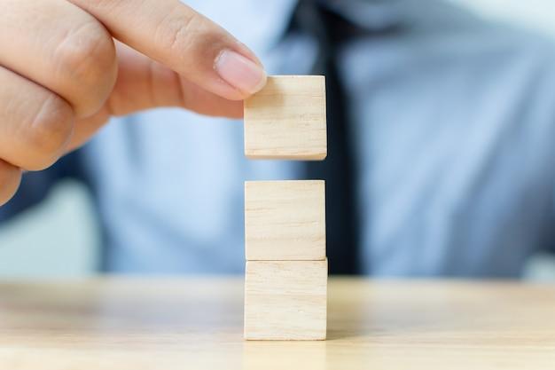 Рука бизнесмена аранжируя деревянный блок штабелируя на верхней части с деревянным столом