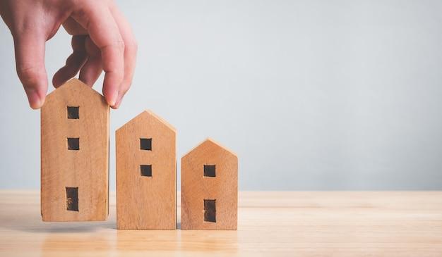 不動産投資不動産と住宅ローンの金融の概念。テーブルの上の木の家を持っている手
