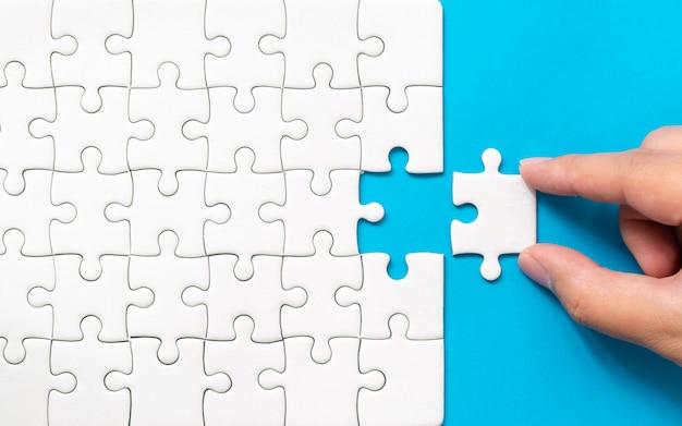 Рука положить кусок белого головоломки на синем фоне