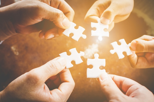 ジグソーパズルを接続する多様な人々の手。パートナーシップとビジネスにおけるチームワークの概念