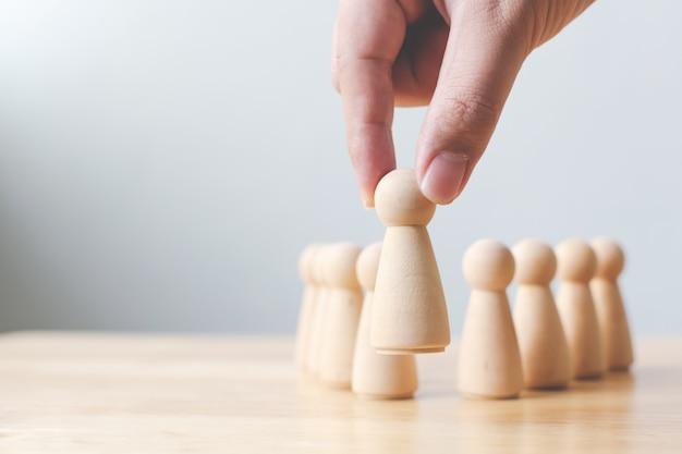 人事、タレントマネジメント、採用担当者、成功するビジネスチームリーダーのコンセプト。手は群衆から目立つ木製の人々を選択します。