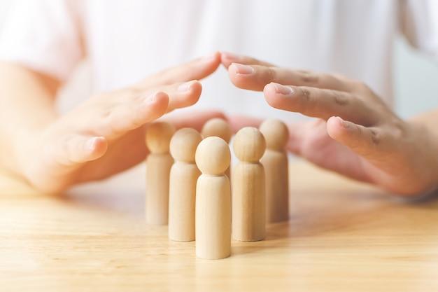 保護の人々の健康と保険の概念。手の盾はテーブルの上の木製の人間を保護します