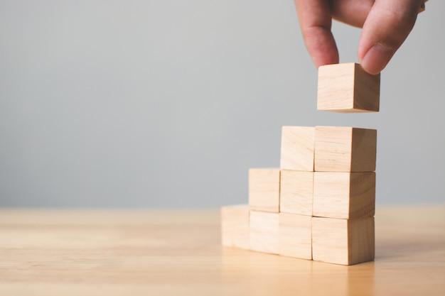 木製のテーブルの上に積み木ブロックを配置する手