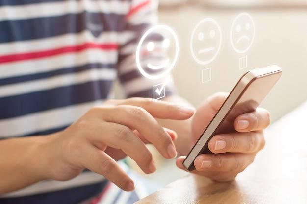 カスタマーサービスエクスペリエンスとビジネス満足度調査。モバイルスマートフォンを使用して男性の手のクローズアップ画像は、顔の笑顔を選択します