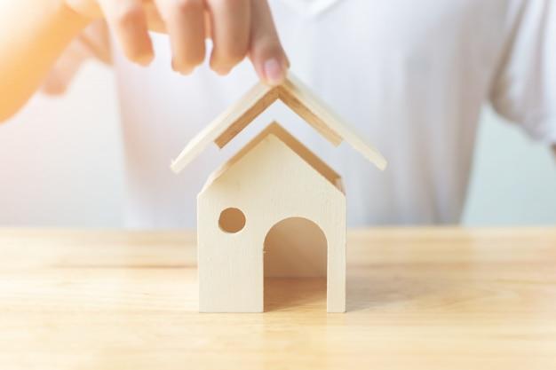 保険の家と不動産投資の不動産の概念のためのお金を節約します。男の手がテーブルの上の大きな木製の家を保護します。