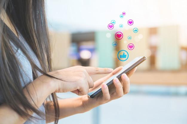 アイコンソーシャルメディアとソーシャルネットワークとモバイルのスマートフォンを使用して女性の手。オンラインマーケティングの概念