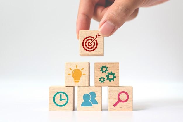 ビジネス戦略と行動計画の概念。アイコンとスタッキング木製キューブブロックを置く手