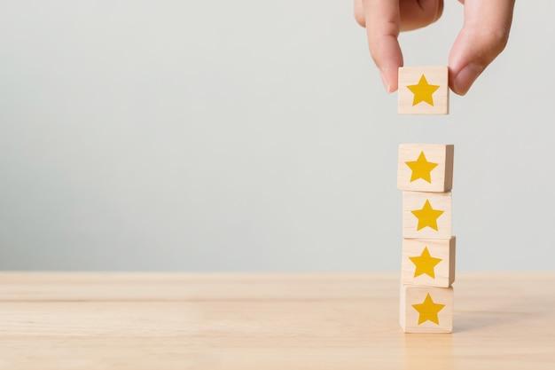 Рука строит деревянный кубик укладки на вершине с пятью звездами