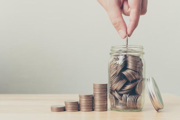 Рука мужчины или женщины, ставящие монеты в банку с деньгами