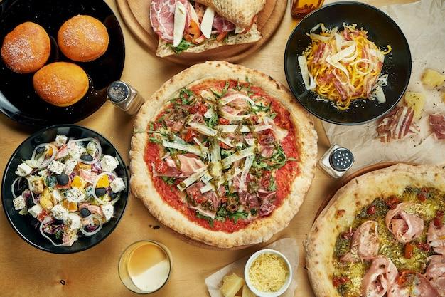 木製のテーブルにさまざまな料理の盛り合わせ。ピザ、パスタ、デザート、ドーナツ、サラダ付きのダイニングテーブル。イタリア料理。トップビュー、食品フラットレイアウト