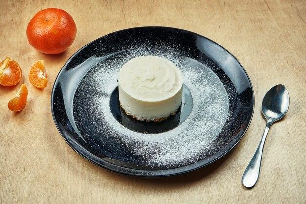 木製のテーブルで繊細な風通しの良いチーズケーキのおいしいスライスにクローズアップ。夕食後に美味しいデザートケーキ。